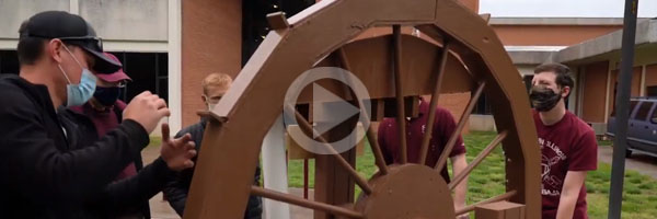 Students with Roman water wheel-based machine